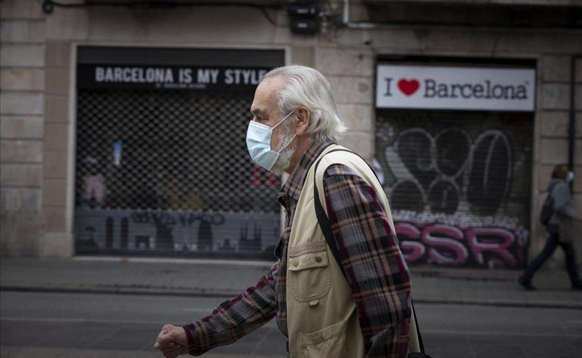 Un paseante, en Barcelona, con locales cerrados.