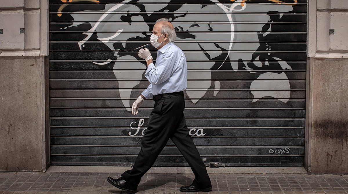 Un hombre con mascarilla pasa junto a comercio cerrado, en València, el 9 de mayo.