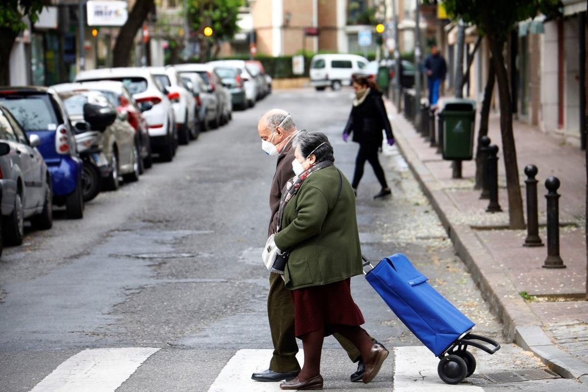 GRAF8927. CÓRDOBA, 18/03/2020.- Dos personas mayores van a la compra protegidas con mascarillas, en la cuarta jornada del estado de alarma por la pandemia de coronavirus, hoy miércoles en Córdoba. EFE/Salas