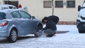 Un hombre coloca las cadenas a su automóvil en el Montseny.