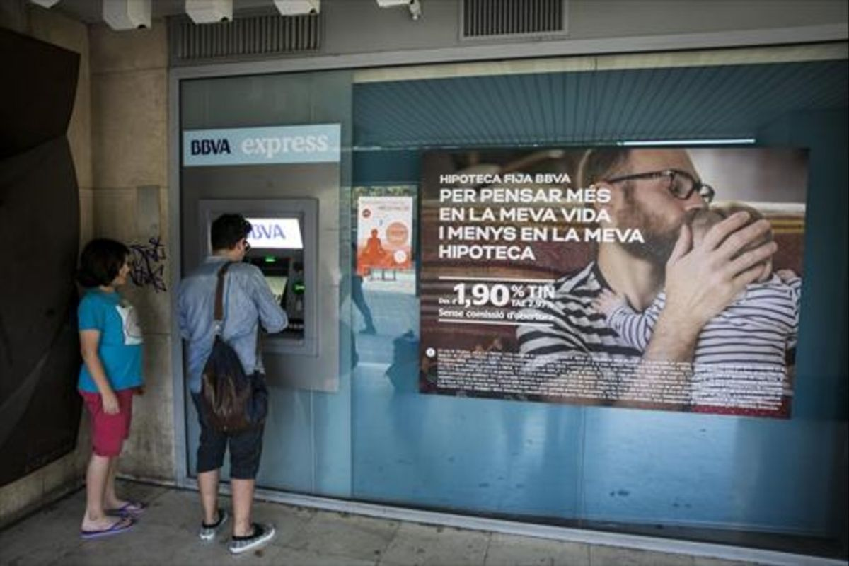 Un cliente de un bancosacando dinero de un cajero automático.