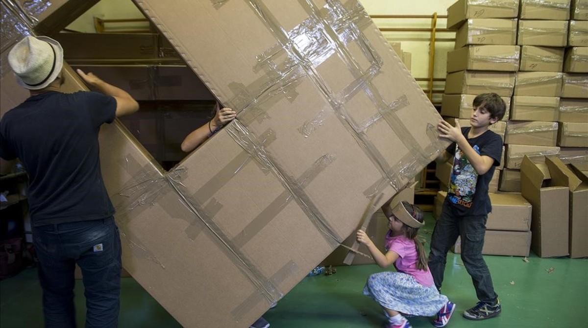 Dos niños ayudan a trasladar cajas de cartón en el Institut Verdaguer, donde se prepara el espectáculo de Olivier Grossetête para las fiestas de la Mercè.