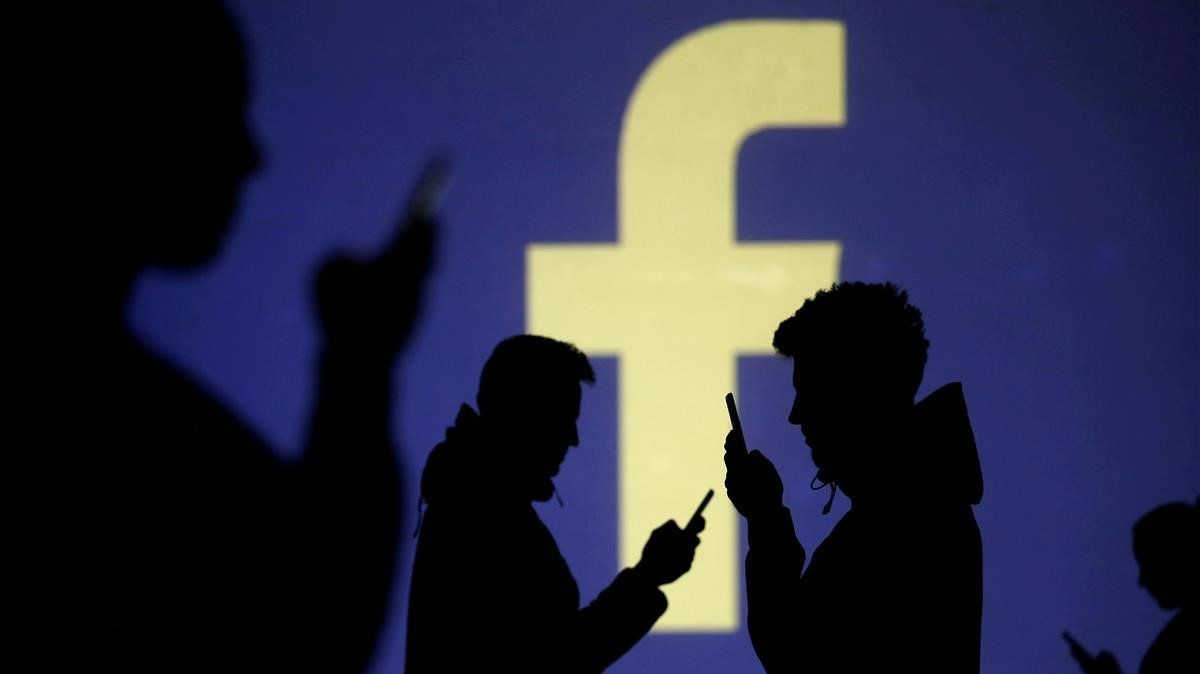 Usuarios de móvil ante el logo de Facebook.