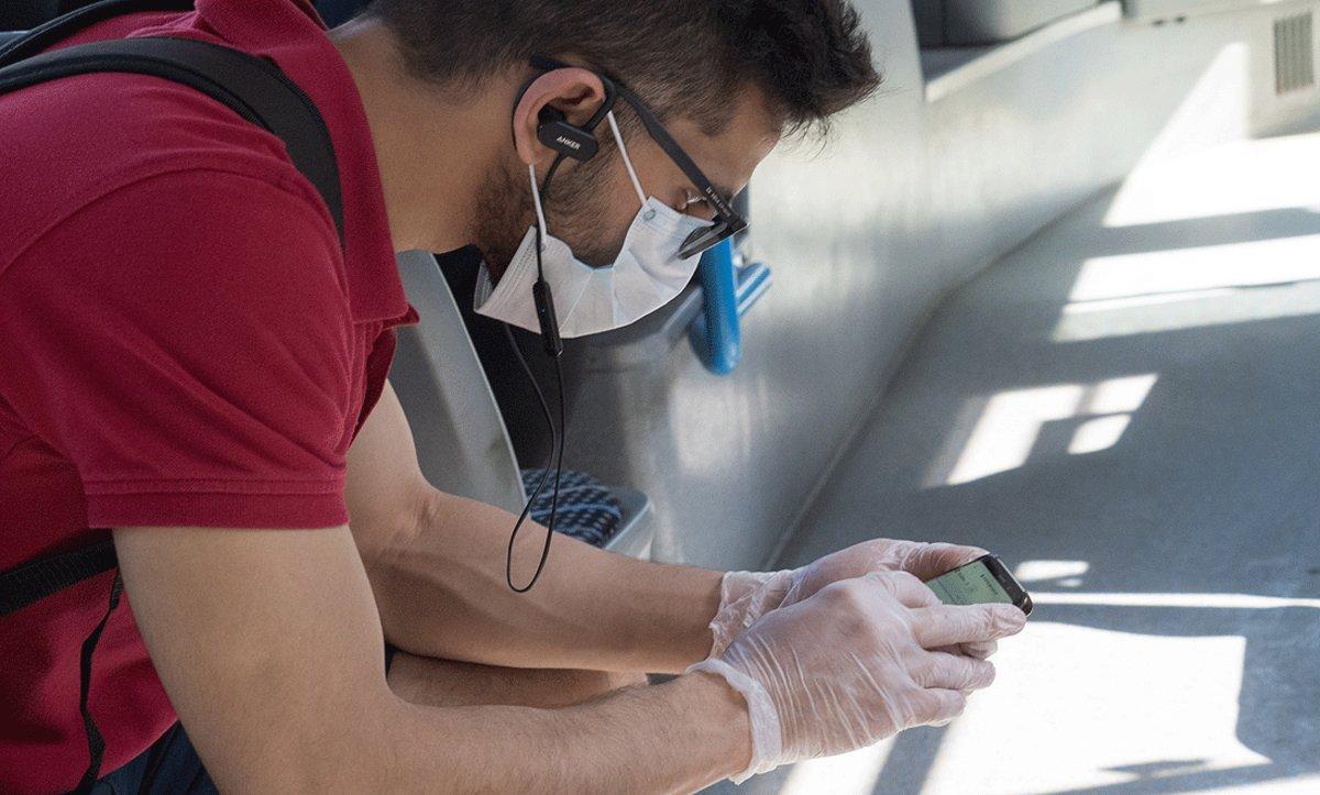 Un joven con mascarilla y guantes consulta su móvil en Budapest (Hungría), el pasado 9 de abril.