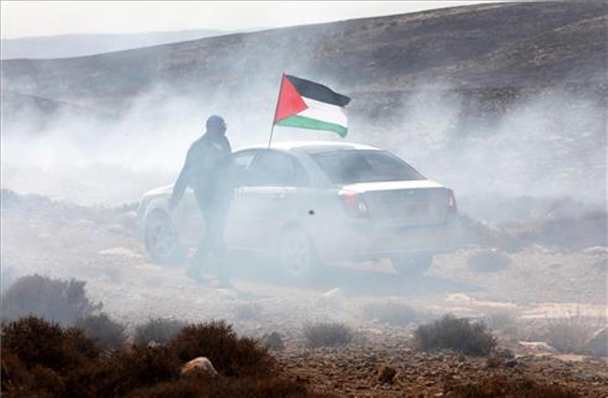 Un hombre ondea la bandera palestina entre gas lacrimógeno en 2019.