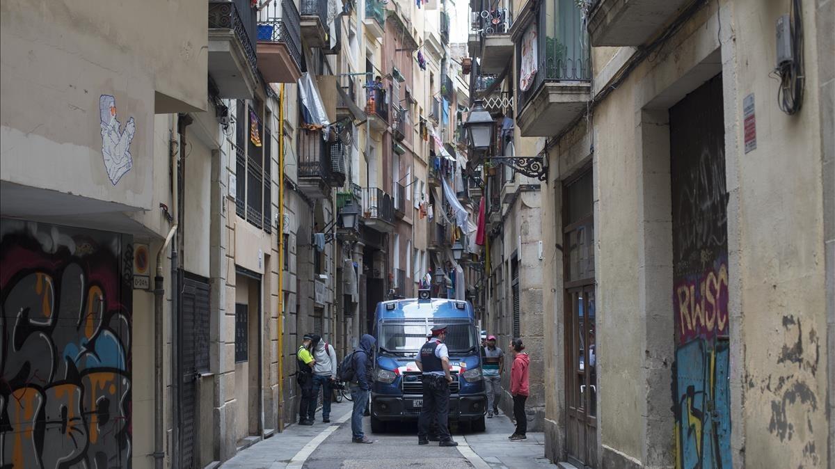La Guardia Urbana y los Mossos d'Esquadra se llevan a uno de los tres detenidos por tráfico de drogas en la finca de En Roig.