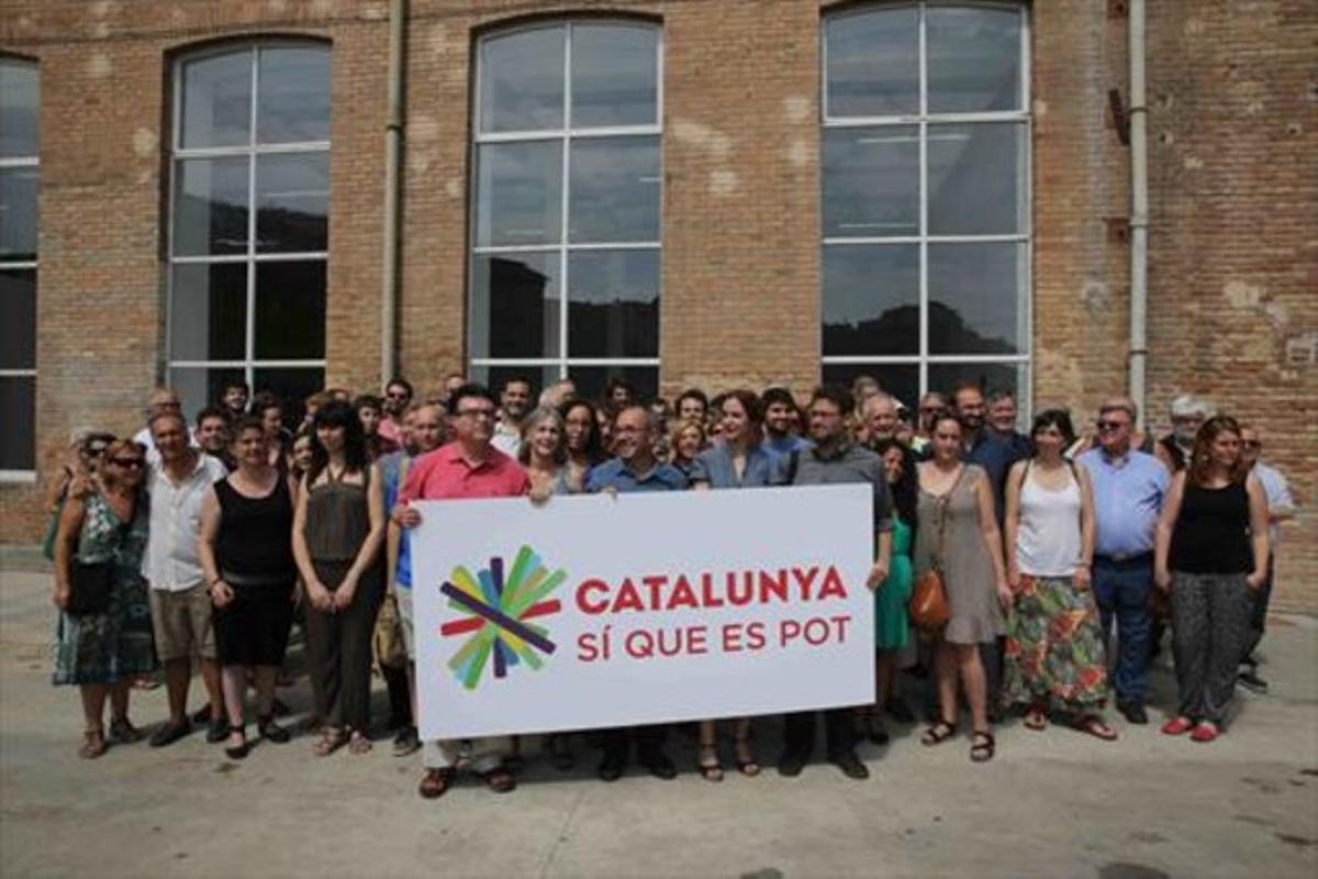 Los impulsores de Catalunya sí que es pot,tras la pancarta con la marca de la confluencia de izquierdas para el 27-S.