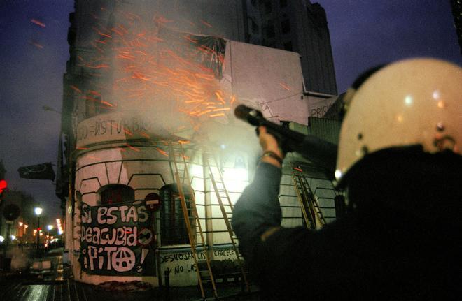 Un policía dispara su escopeta de pelotas de foam durante el desalojo del Cine Princesa en 1996.