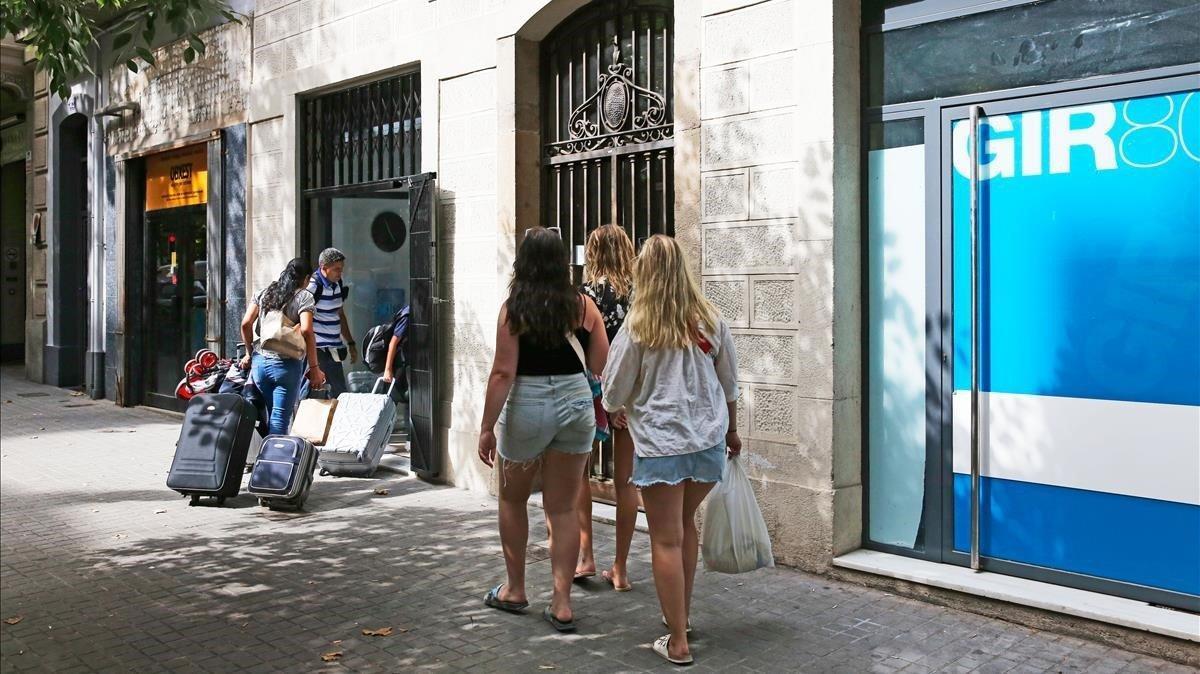 Turistas accediendo a un bloque de pisos turísticos en Barcelona.