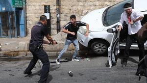 Un policía israelí apunta con un arma a un palestino junto a un judío ortodoxo herido que estrelló su coche cerca de la Puerta de los Leones.