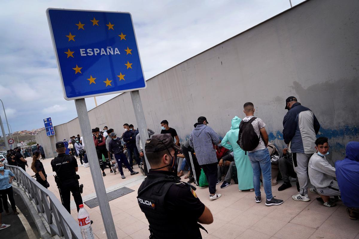 Migrantes esperan, en la frontera del Tarajal, ser devueltos a Marruecos.