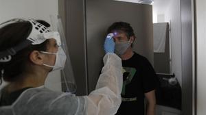 Un sanitario toma la temperatura a un hombre en un hotel de Praga, en la República Checa.