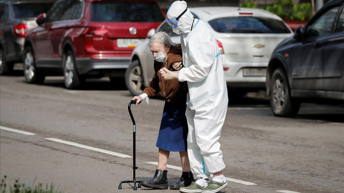 Personal sanitario de Moscú ayuda a una anciana a cruzar la calle