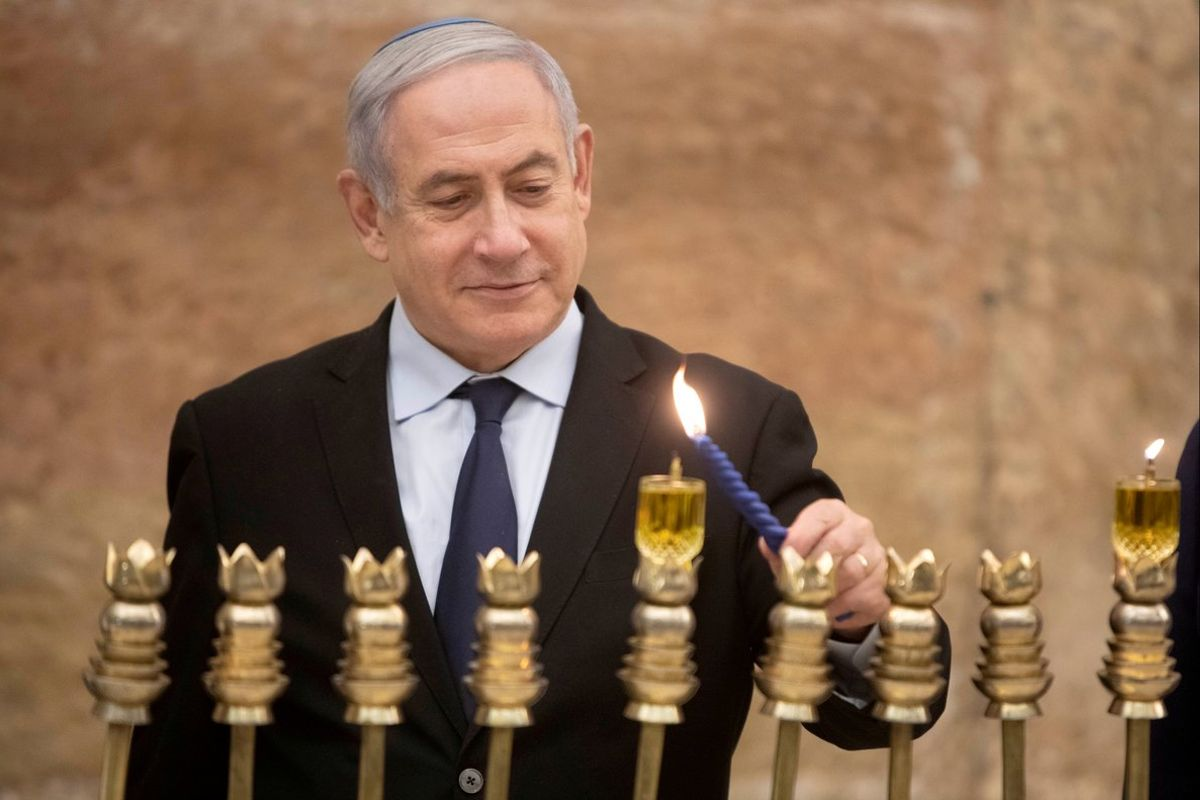 FILE PHOTO: Israeli Prime Minister Benjamin Netanyahu, lights a Hanukkah candle at the Western Wall, the holiest site where Jews can pray in Jerusalem's old city, December 22, 2019. Sebastian Scheiner/Pool via REUTERS/File Photo