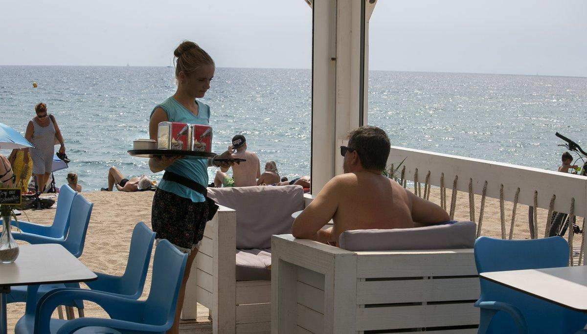Una camarera en un chiringuito de playa trabajando durante el verano, en Badalona.
