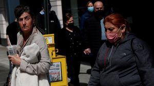 Una mujer camina sin mascarilla por las calles de Manhattan, en la ciudad de Nueva York (EEUU) rodeada de gente que sí la lleva, el pasado 27 de abril.