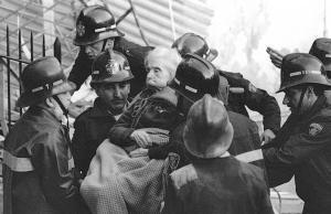 Josep Lluís Fernández (izquierda), con una cruz en su casco, durante el rescate de una anciana tras una explosión de gas, en enero del 91, en la calle Comte Borrell.