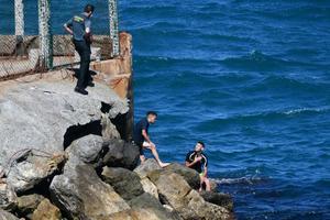 Unos guardias civiles atienden a un marroquí que llegó este lunes a nado a Ceuta.