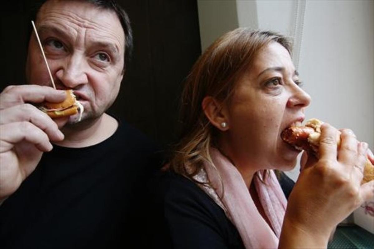 Dos personas comen bocadillos