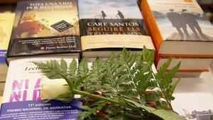 Una rosa blanca, símbolo este año de esperanza, homenaje a los sanitarios y recuerdo a las víctimas del covid,rodeada de libros, en la librería Laie de Barcelona, este martes.