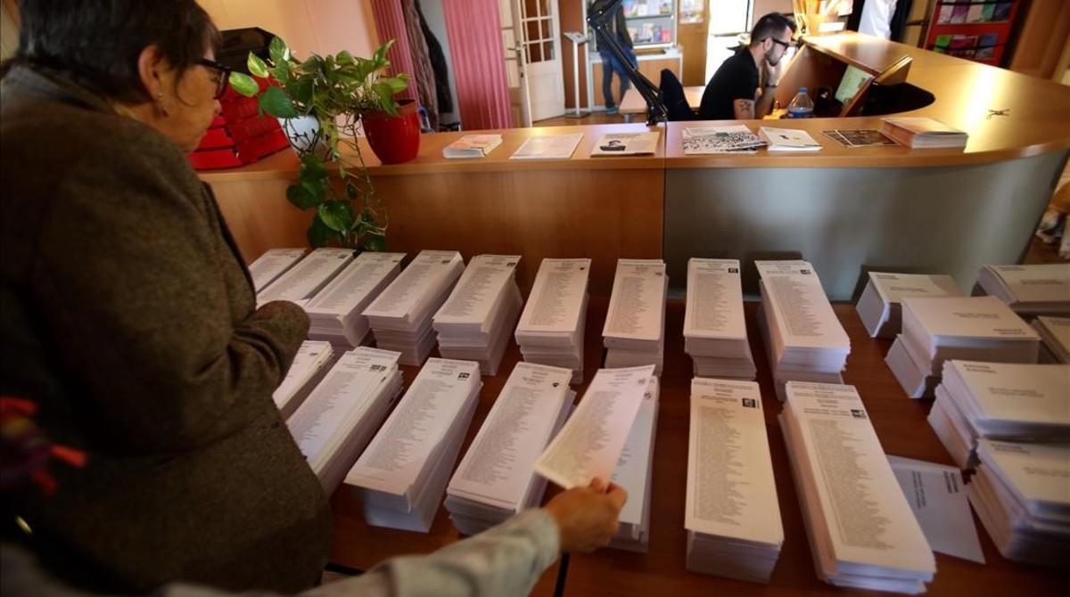 Una mujer busca su papeleta electoral en los comicios del 27-S.