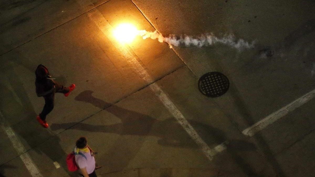 Los manifestantes reaccionan después de que se arrojaron gases lacrimógenos durante una protesta en el centro de Des Moines.