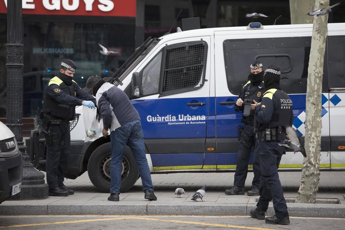 La guardia urbana multa a un hombre que no dejaba de dar de comer a las palomas en la Plaza de Cataluña, a pesar de las advertencias.