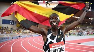 Cheptegei, ufano con la bandera de Uganda tras batir la marca de Bekele en el 5.000 en Mónaco.