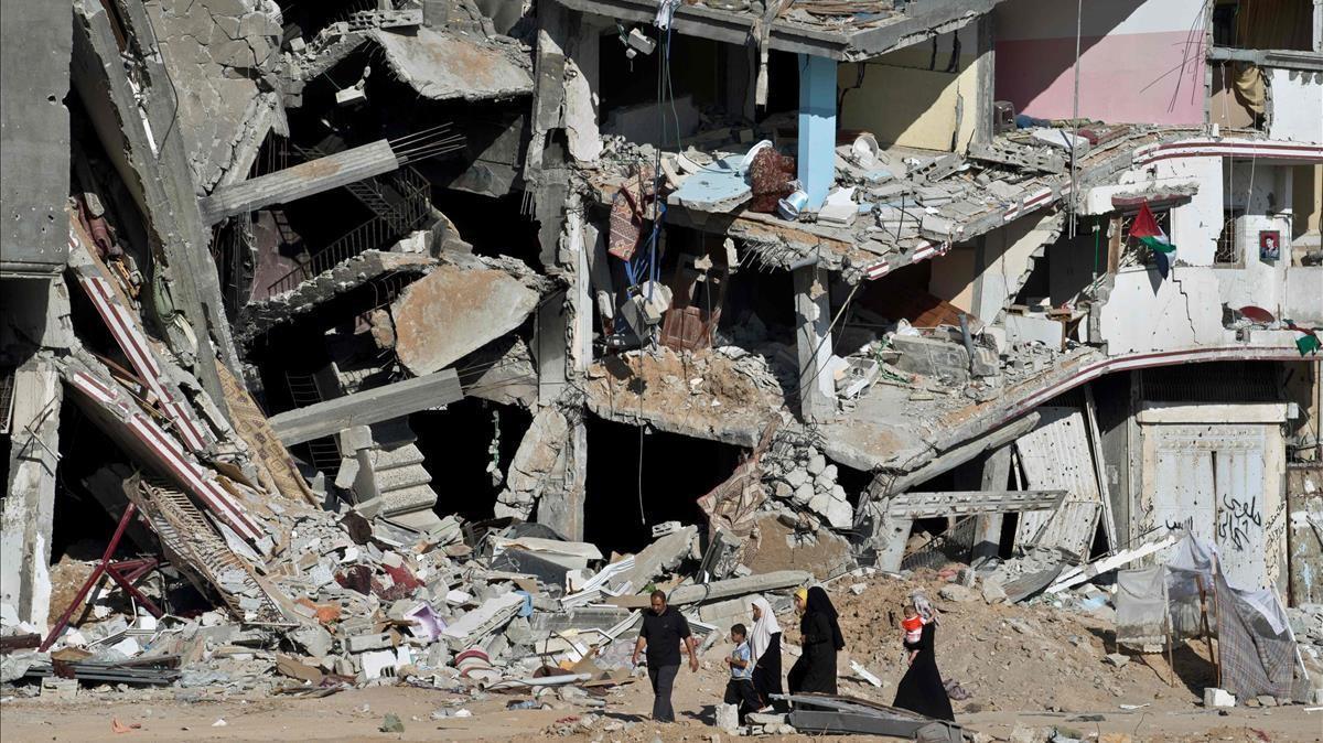 Una familia atraviesa una calle con edificios destrozados en Gaza, en el marco del enfrentamiento entre Hamás e Israel en 2014.