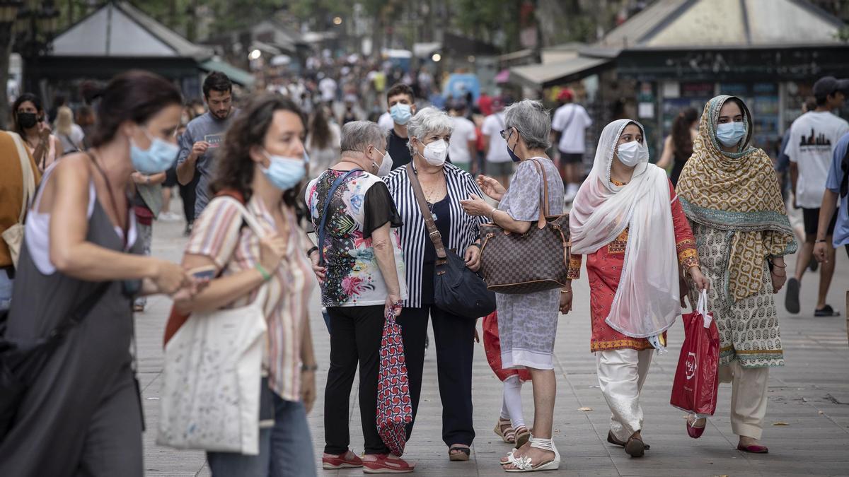 Gente paseando con mascarilla y sin mascarilla en La Rambla de Barcelona.