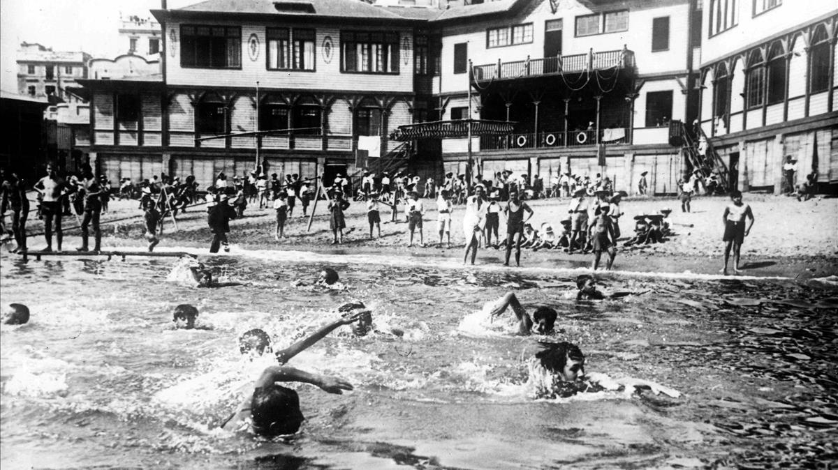 La Escola del Mar, al fondo, obra de Josep Goday, y varios de sus alumnos, en primer plano, en la hora del baño.