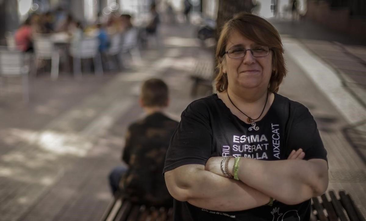 Olga Martínez posa en una plaza de L'Hospitalet, con su hijo menor (de espaldas) tras ella.