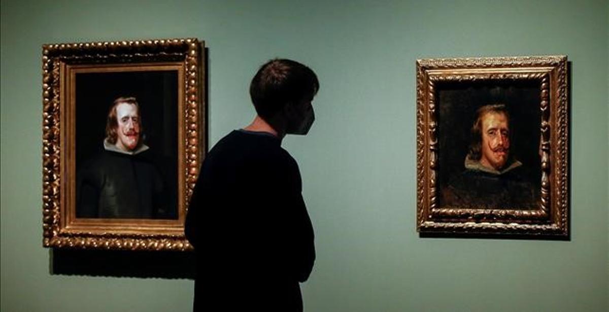 Un visitante observa, ayer en el Museo Picasso, la copia de Felipe IV realizada por Pablo Picasso (d) junto al cuadro original de Velázquez (i), conformando una exposición de 19 cuadernos del artista malagueño de sus inicios.