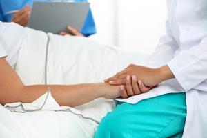 Una doctora da la mano a una paciente enferma en un hospital para animarla.