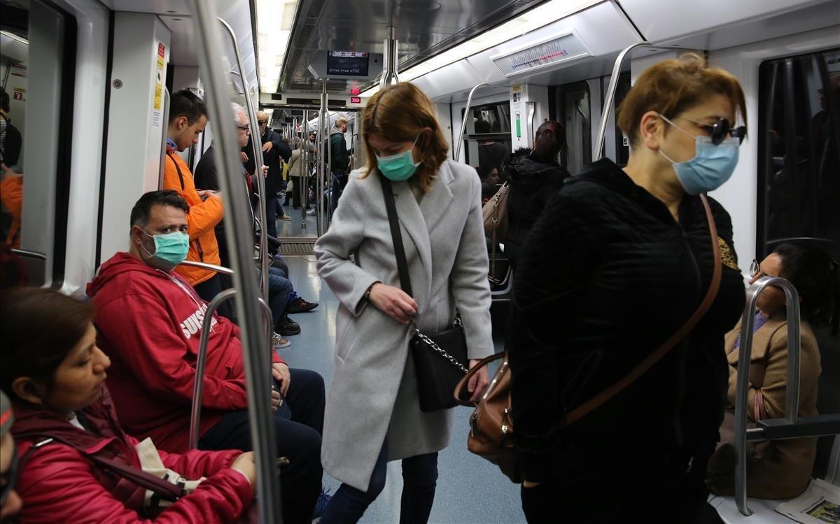 Pasajeroscon mascarilla por el riesgo de coronavirus en el metro deBarcelona.