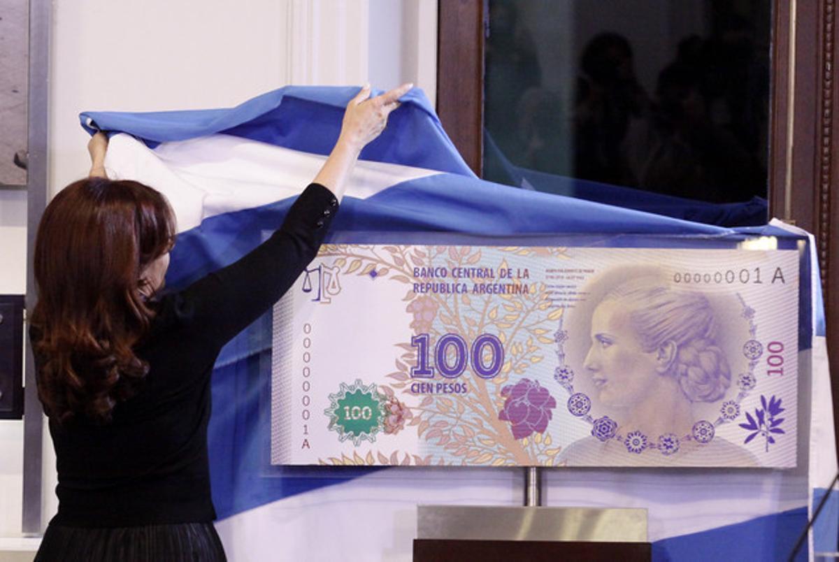 La presidenta Cristina Fernández de Kirchner descubre una imagen del nuevo billete de 100 pesos, con la imagen de Eva Duarte de Perón, en julio pasado.