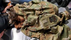 Un niño afgano duerme en el suelo de carga de un C-17 Globemaster III de la Fuerza Aérea de EE. UU.