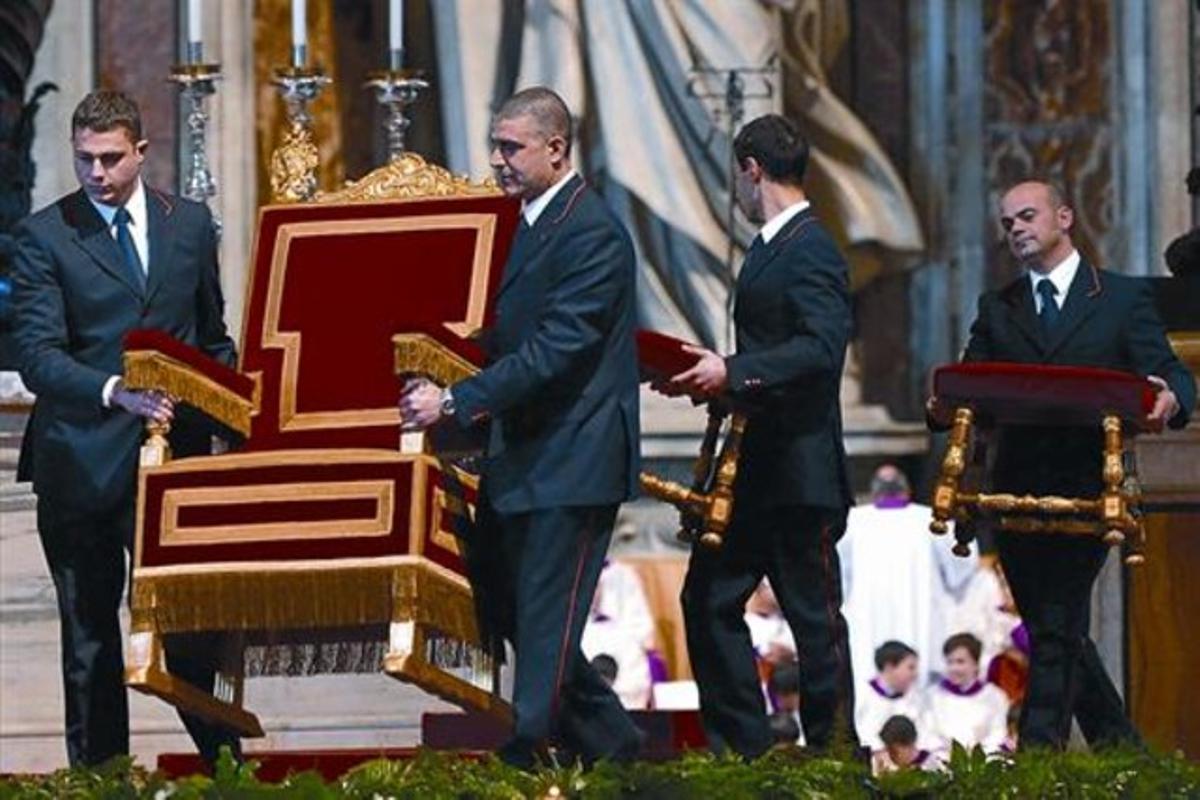 Unos asistentes mueven la silla del Papa en la basílica de San Pedro, ayer.