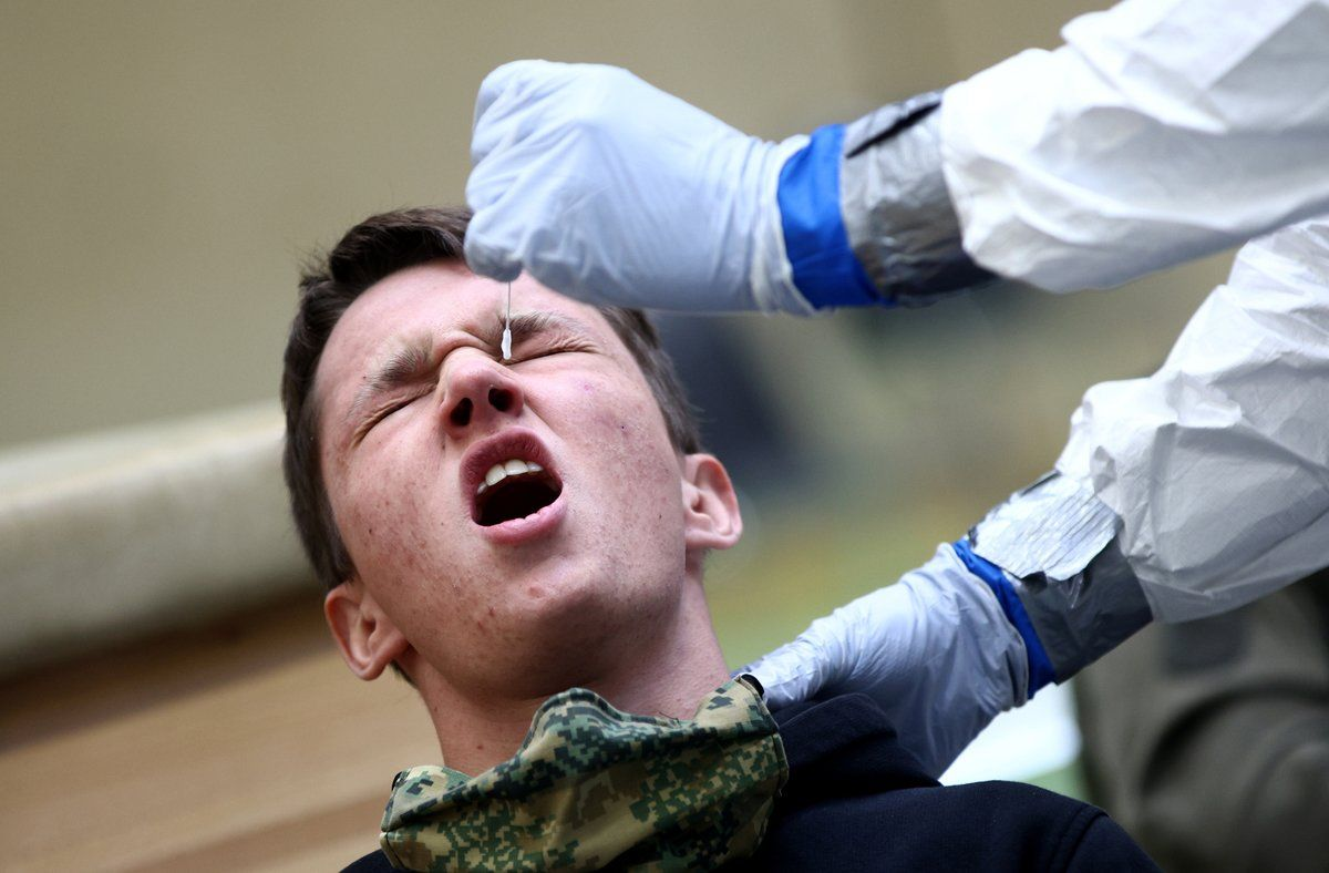 A person reacts as a doctor takes a swab from his nose for an antigen rapid test at a mass testing station operated by the Austrian armed forces during the coronavirus disease (COVID-19) outbreak in Korneuburg, Austria, November 27, 2020. REUTERS/Lisi Niesner