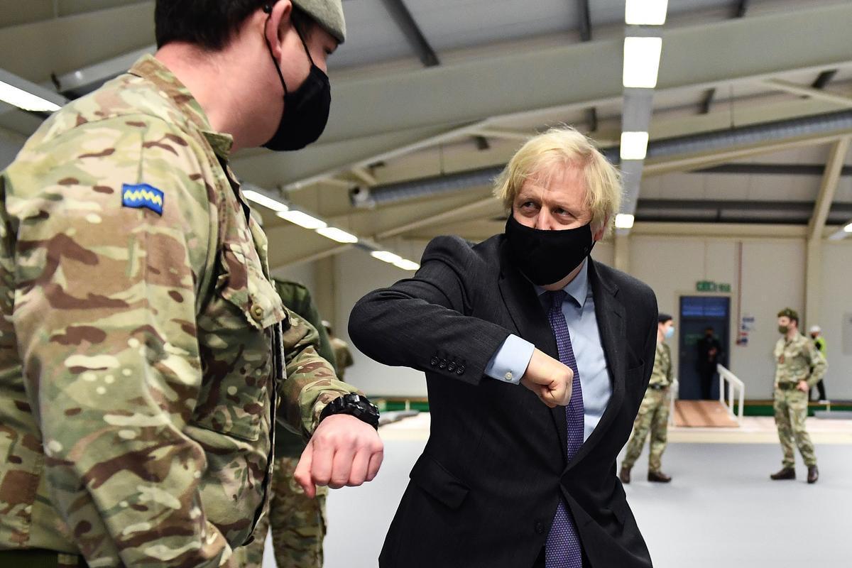 El primer ministro británico, Boris Johnson, saluda a un militar en un centro de vacunación abierto en la ciudad escocesa de Glasgow.
