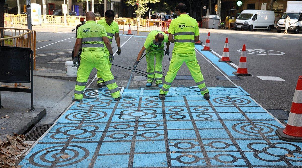 Un grupo de operarios pintan parte de la calzada de la calle de Rocafort de Barcelona para ampliar el espacio destinado a los peatones, el pasado 2 de julio.