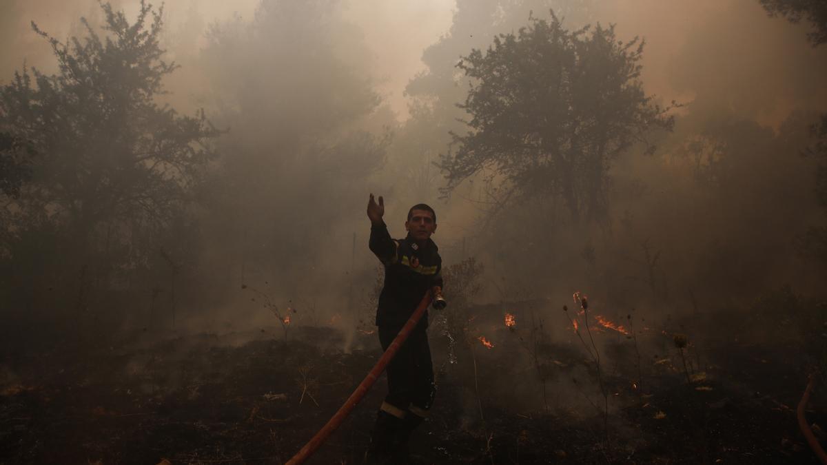 Un bombero combate un incendio en Stamata, en el noreste de Atenas (Grecia).