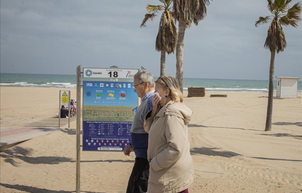 Una pareja pasea este viernes por la playa de Gandia, donde ha habido un repunte en la llegada de turistas madrileños