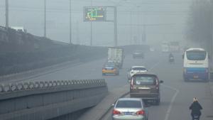 Varios vehículos circulan por una carretera llena de polución, este viernes, en Pekín.