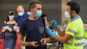 Un enfermero pone la vacuna Pfizer a un hombre, este viernes, en el Estadio Nueva Condomina de Murcia.