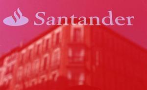 Banco Santander pierde 8.771 millones en el 2020 por provisiones y saneamientos. En la foto, el logo de la entidad reflejado en un cristal en un edifico de Madrid.