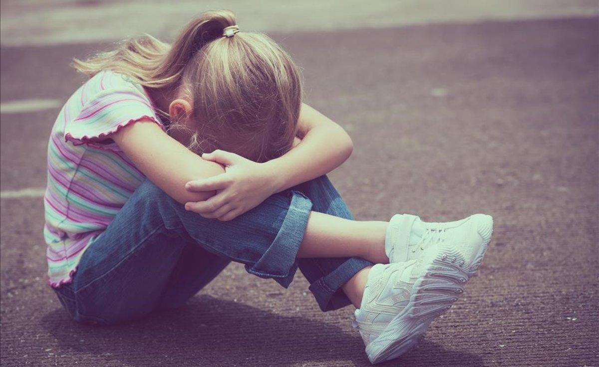 Una niña llora en el suelo.