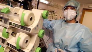 Una enfermeradel hospital CHU de Liege (Bélgica) sostiene equipos médicos mientras trataa pacientes que padecen la enfermedad del coronavirus.
