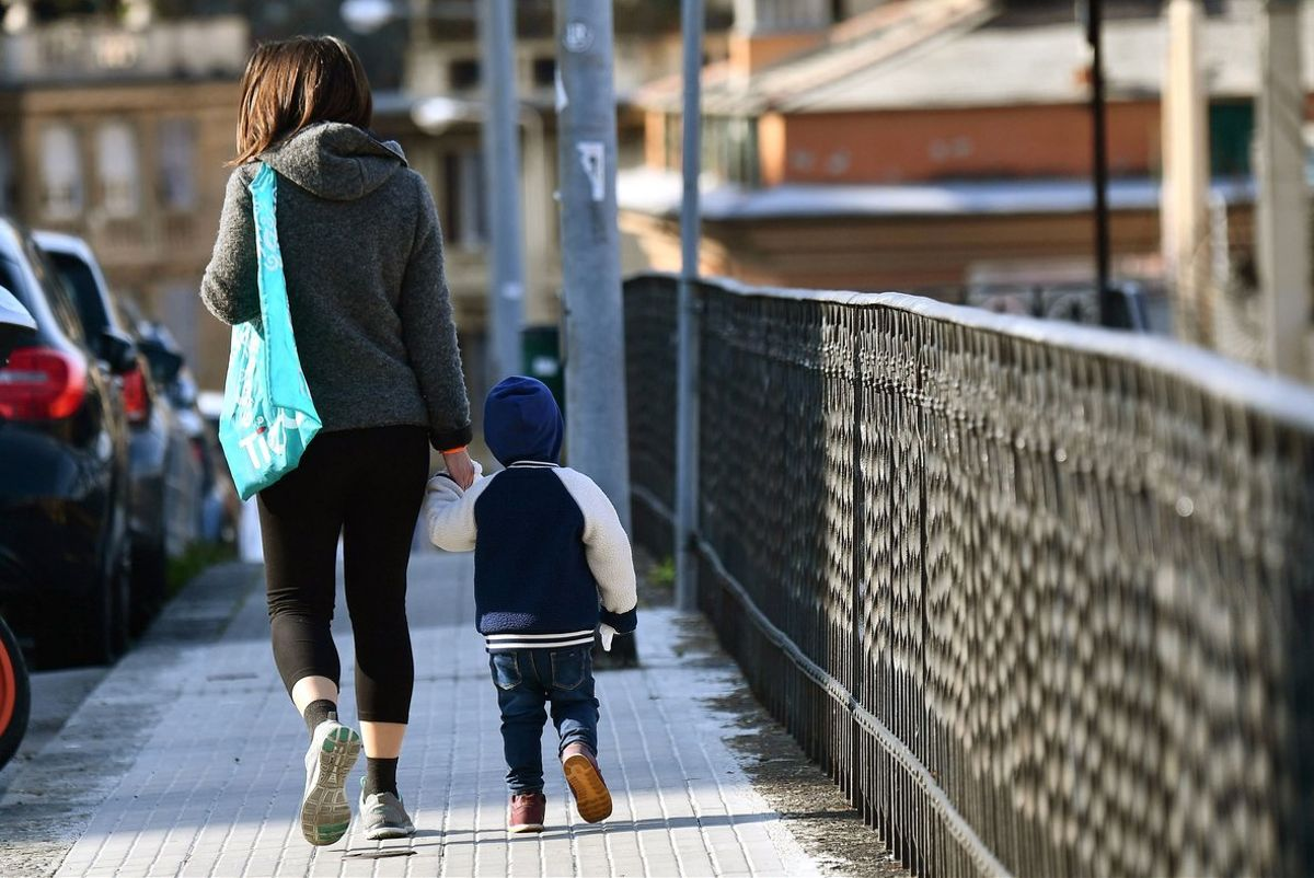 Genoa (Italy), 30/03/2020.- A yhoung woman and a toddler walk along a street as all playgrounds for children remain closed and empty due to the rules against the spread of the SARS-CoV-2 coronavirus which causes the COVID-19 disease, in Genova, Italy, 30 March 2020. Countries around the world are increasing their efforts nd measures to stem the widespread of the disease. (Italia) EFE/EPA/LUCA ZENNARO