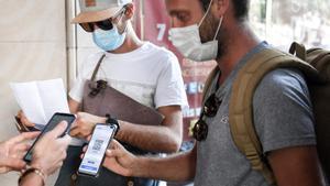 Unos espectadores enseñan su pasaporte sanitario antes de entrar al cine en París.